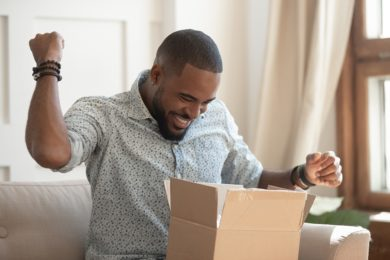 Excited african man customer receive open parcel box at home